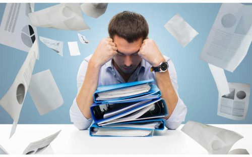 Stressed teacher over piles of paper work